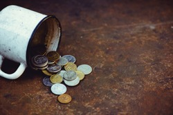 the fall of the Russian ruble, poverty and poverty scattered coins in the old mug on a rusty background, sanctions.