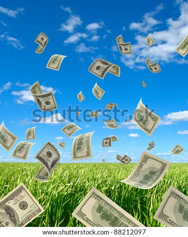 The Falling cash on 100 dollars, on background sky and herbs. - stock photo