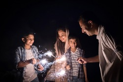 The family enjoying the sparkle firework as part of the celebration of a festival.