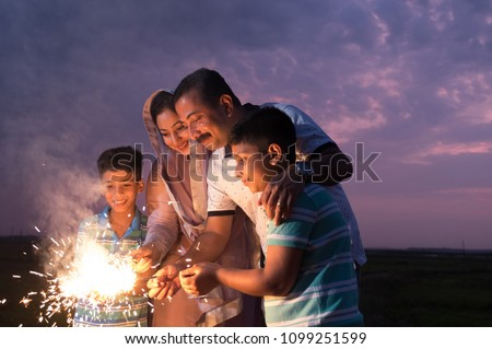 The family enjoying the sparkle fireworks as part of the celebration of a festival - Shutterstock ID 1099251599