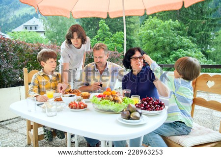 The family from five persons have got dinner on summer terrace in sunny day