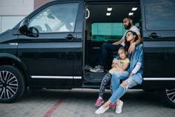 The family goes on a trip with minivan. Happy family sitting in vip van car
