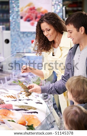 The family in shop at seafood chooses meal