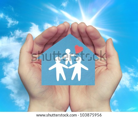 The family in the house. Hands holding a house with a happy family against the backdrop of the sunny sky.