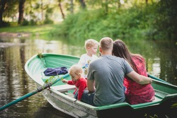The family is floating on the lake in a boat with oars in the park, dad hugs mom, the girl looks into the water and holds a twig.