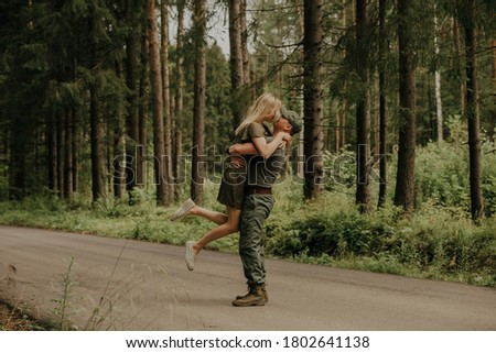 The family is walking in a pine forest. Man who returned home from the army, love on a summer day, outdoor recreation, date on nature.