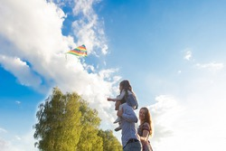 the Family launches kite against beautiful sky