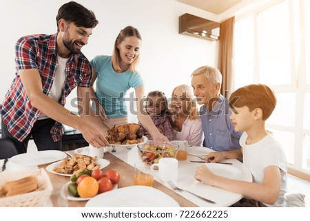 The family sits down for dinner on Thanksgiving. The man serves a festive turkey, his wife stands beside him and serves a salad, the rest sit and look forward to #722662225