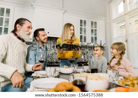 The family sits down for dinner on Thanksgiving. Young woman serves a festive turkey with a salad, grandfather, father and children sit and look at the tasty food and smile