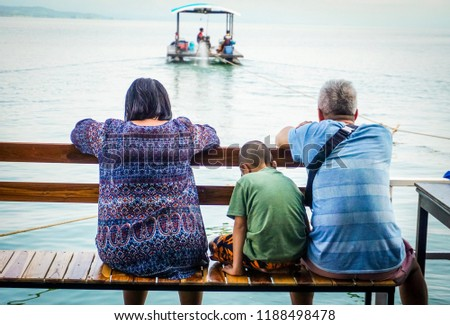 The family sitting at the balcony of the raft and looking to towboat.