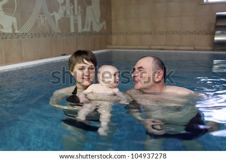 The family swimming in an indoor pool
