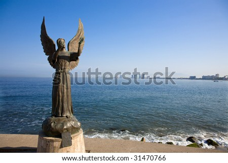 The famous Angel of Hope and Messenger of Peace statute in Puerto Vallarta Mexico created by artist Hector Manuel Montes Garcia, greets visitors to the Malecon.