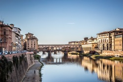 The famous bridge is the Old Bridge (Ponte Vecchio) in Florence. View from the Arno river embankment. Florence, Tuscany, Italy