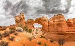 The famous Broken Arch in the Arches National Park, Utah and dramatic dark clouds