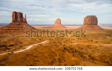 The famous Buttes of Monument Valley Navajo National park, Utah, USA with car driving dirt road giving perspective of huge scale of the Buttes and the Valley