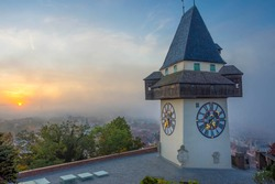 The famous clock tower on Schlossberg hill, in Graz, Styria region, Austria, at sunrise. Beautiful foggy morning over the city of Graz, in autumn