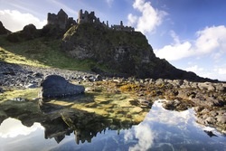 The famous Dunluce Castle - a UNESCO landmark from the Causeway Coast of Northern Ireland - reflected in a tidal pool from beneath the cliffs.