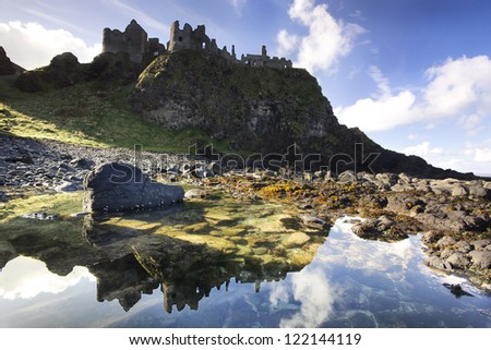 The famous Dunluce Castle - a UNESCO landmark from the Causeway Coast of Northern Ireland - reflected in a tidal pool from beneath the cliffs. - stock photo