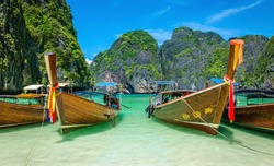 The famous heavenly beach Maya Bay on Phi Phi Islands with colorful longtail boats and limestone hills in the background, Thailand