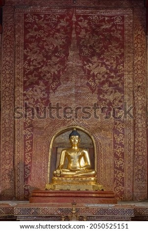 The famous historical Phra Singh Buddha gilded statue with beautiful old red and gold stencil background decor inside Viharn Lai Kham at landmark Wat Phra Singh buddhist temple, Chiang Mai, Thailand