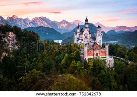 The famous Neuschwanstein castle during sunrise, with colorful panorama of Alps in the background