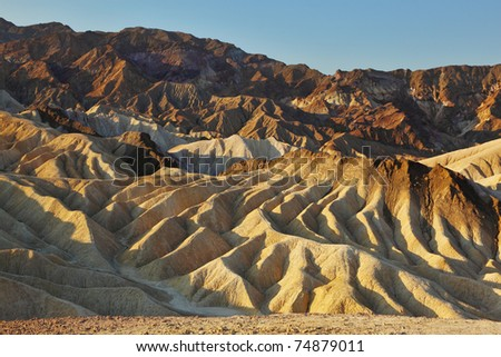 The famous section of Death Valley in California - Zabriskie Point. Picturesque hills of pink, yellow and chocolate hues at sunset - stock photo