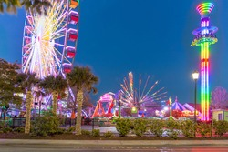The famous Sky (Ferris) Wheel and other thrill carnival rides at the Boardwalk during twilight hours. Located in downtown Myrtle Beach, South Carolina.