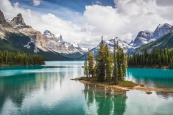 The famous Spirit Island of Maligne Lake in Jasper National Park of Alberta, Canada. Vivid blue-green waters of the glacially fed lake shine in the sunshine around the famous gathering of pines.