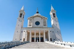 The famous symmetric catedral in Piedmond, Italy, dedicated to saint Giovanni Bosco, a famous italian educator. The statue is in the centre and bell towers on each side. Stairway in the foreground.