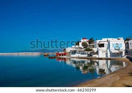 The famous Tavern on the sea mirror of the bay of the island of Mykonos with a red boat and the church
