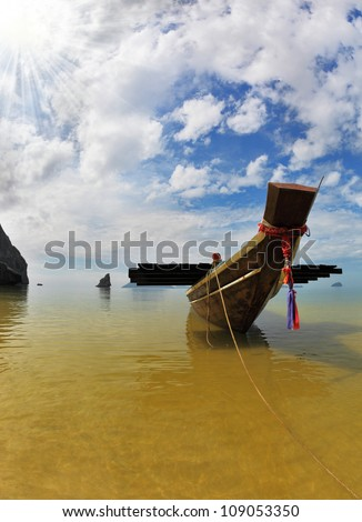 The famous Thai Longtail boat mooring anchor in the sand. The picturesque sandy beach on an ocean island. Thailand