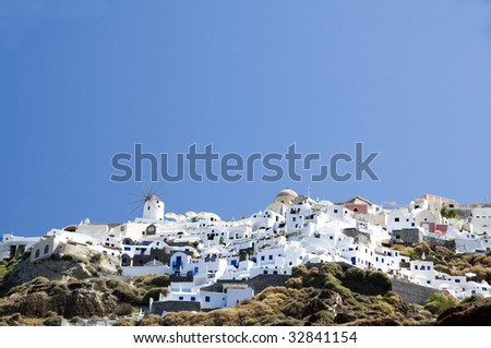 the famous town of oia ia santorini built into the caldera volcanic cliffs over the mediterranean sea as seen from amoudi port in the cyclade greek islands