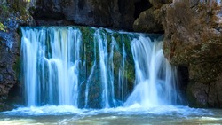 the famous waterfall atysh flowing from a karst funnel in the Ural mountains of Bashkortostan on an autumn sunny day. blur of moving water of a waterfall.