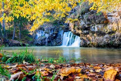 the famous waterfall atysh flowing from a karst funnel in the Ural mountains of Bashkortostan on an autumn sunny day.