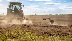 The farmer drove a plow to improve the soil, preparing for the upcoming cropping season on dry ground until the dust was dispersed in the air.