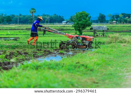 The farmer with a tractor after the rainy season to start walking-but to sow the. Thailand farmers around everywhere are starting to plow their rice-Lampang Thailand #296379461