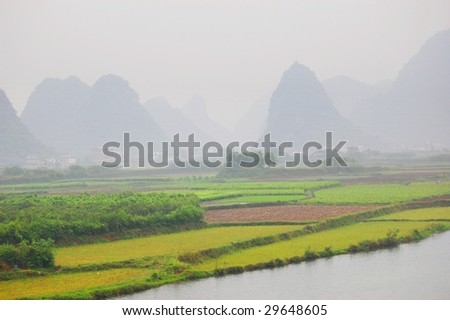 The farmland with mountains in the misty background