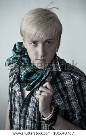 the fashionable and impudent young guy on a gray background