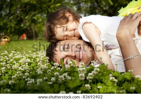 The father and the daughter together lay on a grass