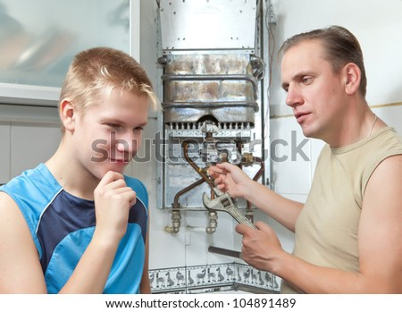 The father and the son-teenager together in  repair a gas water heater.