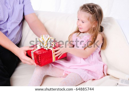 The father gives his young daughter in a red gift box with a white ribbon.