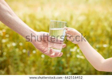 The father gives the child a glass of water. Selective focus.  - Shutterstock ID 662516452