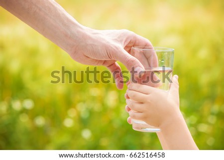 The father gives the child a glass of water. Selective focus.  - Shutterstock ID 662516458