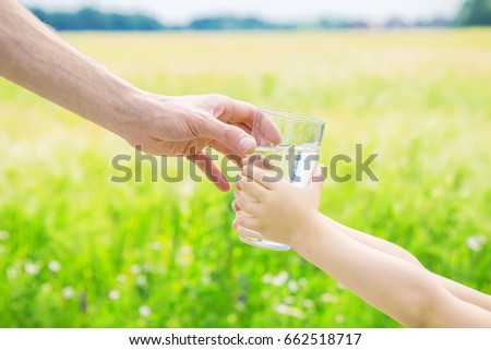 The father gives the child a glass of water. Selective focus.  #662518717