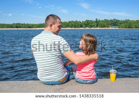 The father having embraced the daughter sit on the embankment against the background of the river in sunny summer day. Family day off. #1438335518