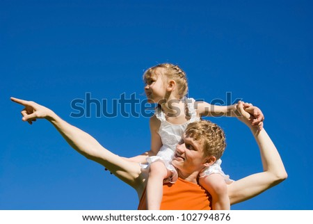 The father holds the daughter on his shoulders, and indicates