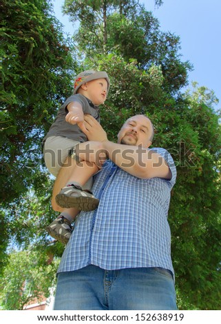 the father keeps on hands of the little boy in a hat