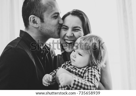 The father, mother holds little girl on background white wall indoor. Portrait of mom, dad and daughter. The concept of family holiday. Man kisses his wife. upper half. Close up. black white photo.