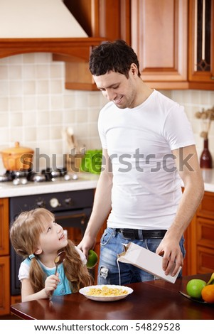 The father pours milk in corn-flakes of the small daughter