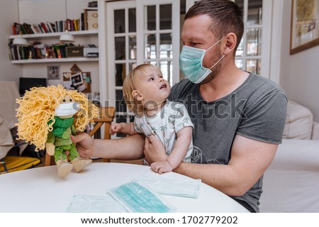 The father sits in a medical mask and tells the child about how to wear a mask and how to protect yourself from the virus. He is holding a doll, which is also wearing a mask.The child is scared.